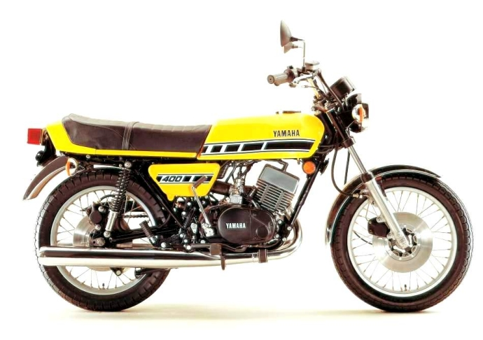 Factory official release picture of bright yellow Yamaha RD400 motorcycle from profile
